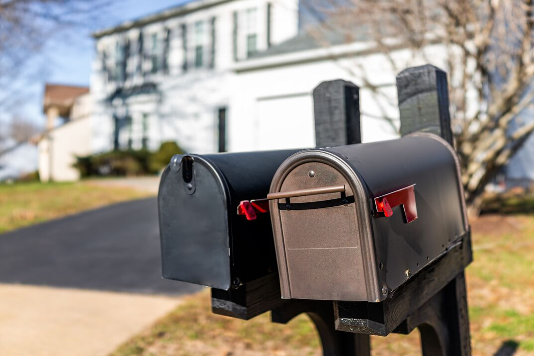 Closeup of two modern black and brown metal red flag mailboxes at single family home in residential suburbs with nobody and house in background