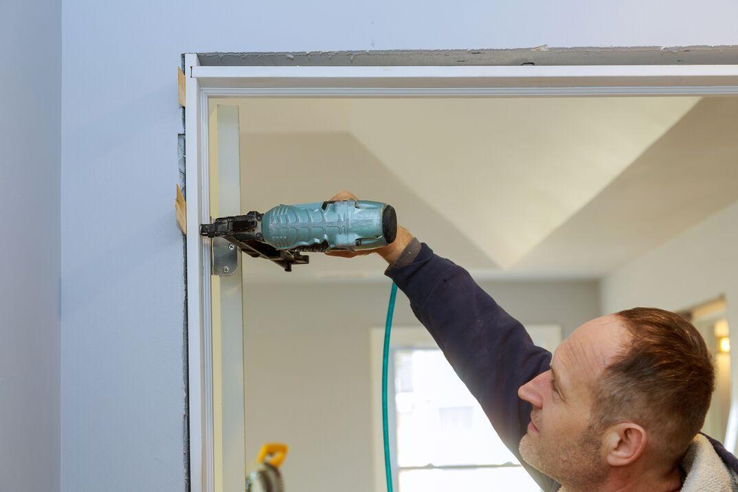 Contractor using pnumatic nail gun installing the interior door of apartment