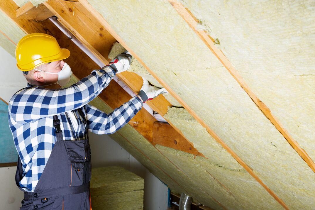 man wearing PPE installing fiberglass insulation in an attic space.
