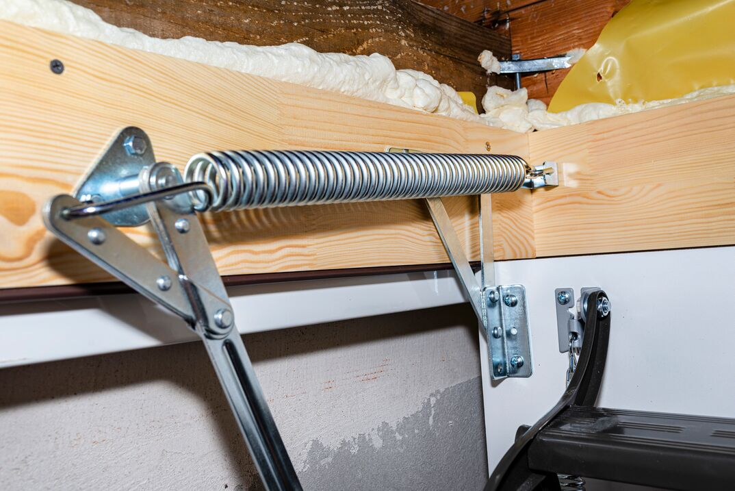 close up image of an attic ladder s spring assembly