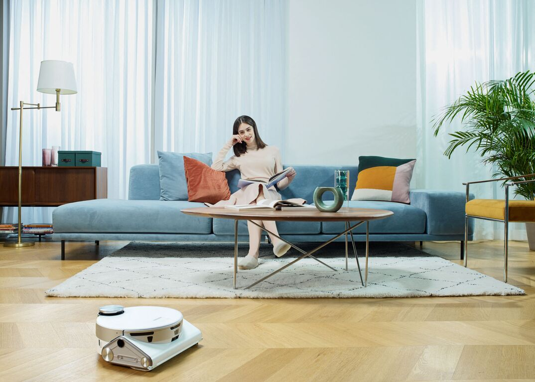 Samsung JetBot 90 AI Plus cleans beige hardwood floor aw woman sits on light-blue couch with her feet on a white area rug in front of a coffee table and next to a side chair.