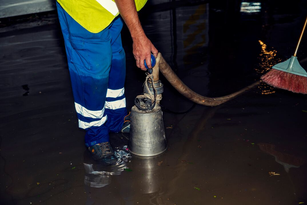person stands ankle deep in water while submerging a sump pump