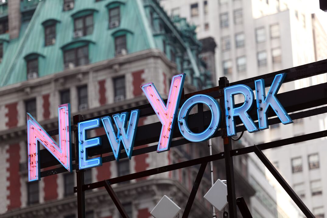 Illuminated New York sign with city buildings in background