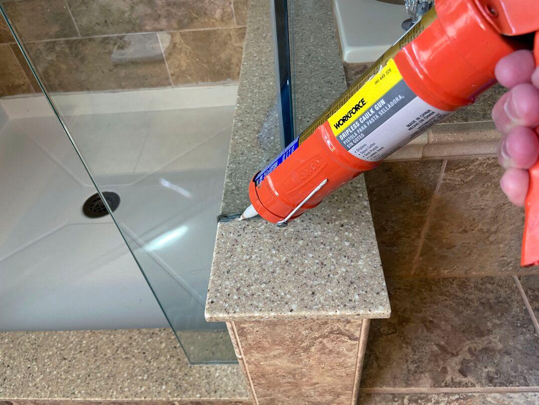 handyman installing glass shower doors and applying sealant