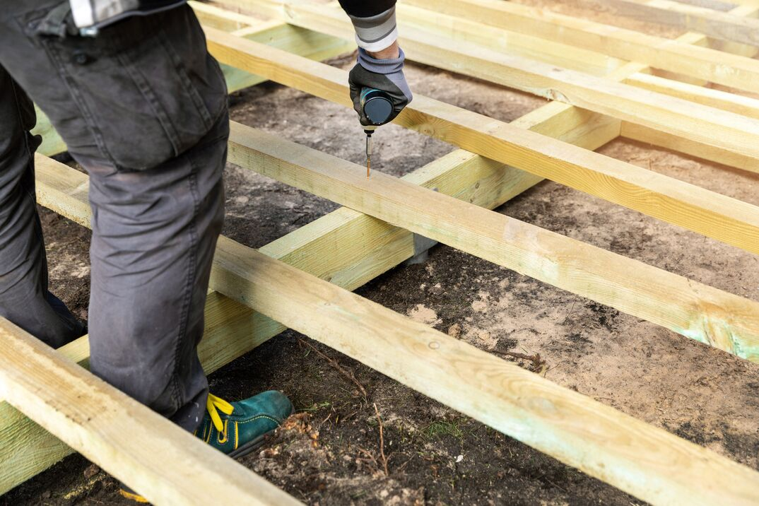 Male construction worker building a wooden deck frame for a resideential terrace deck