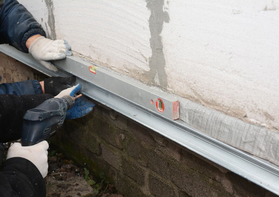 Old house foundation wall repair and renovation  with installing metal sheets for waterproofing and protect from rain  Contractors with Foundation repair