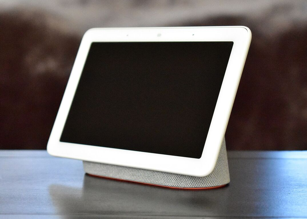 A white Google Nest Home device with blank, black screen rests on a table.