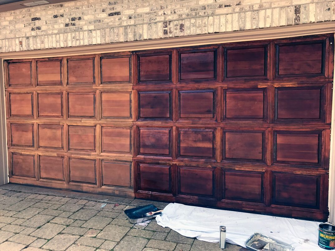 Unfinished red oak garage door with stain being applied.