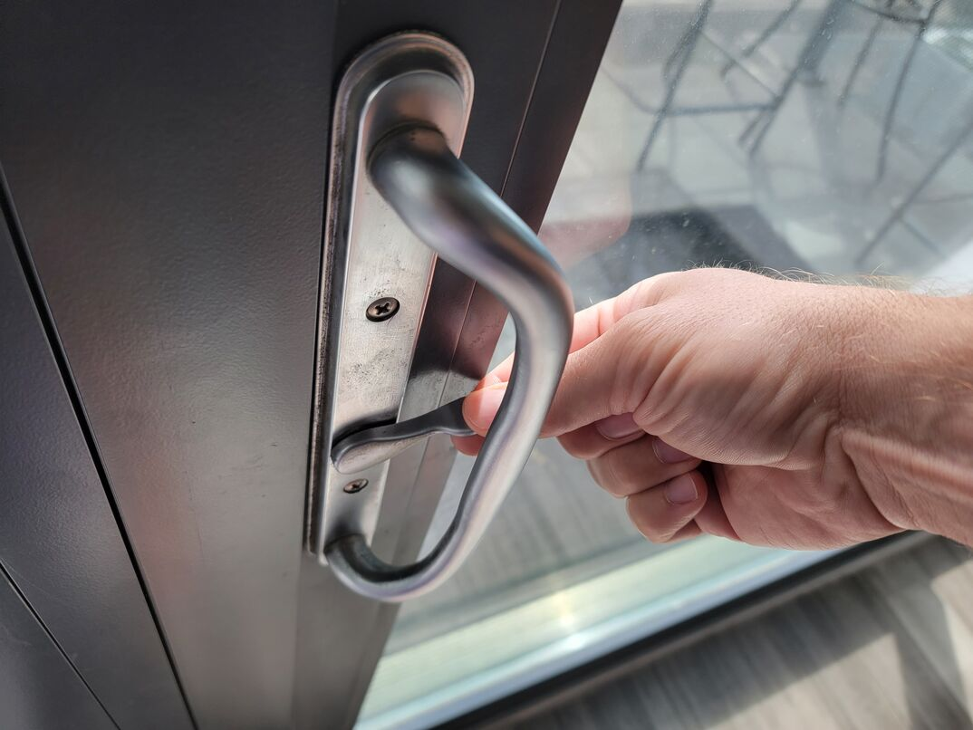 Human hand flipping the switch to lock a sliding glass door from the inside of a home