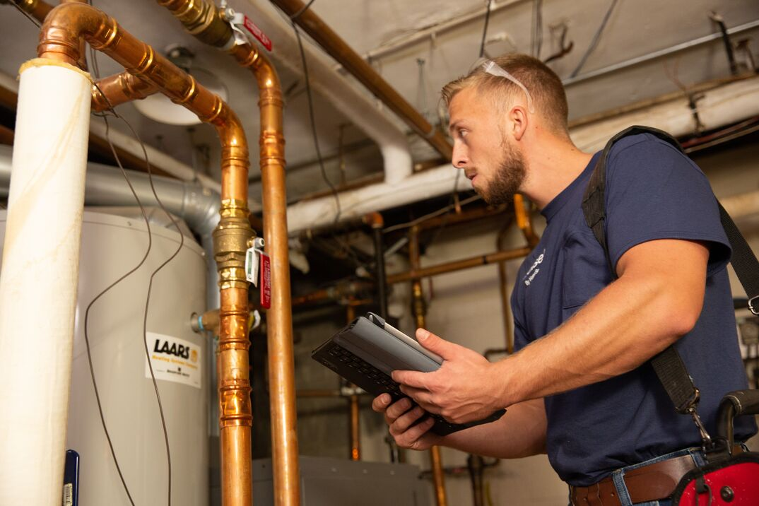a young technician wearing a blue shirt and safety glasses atop his head, takes a look at a water heater before an inspection
