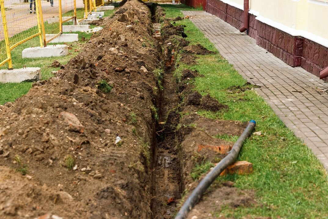A long and deep trench dug up in a yard to lay in a drainage pipe for a trench drain