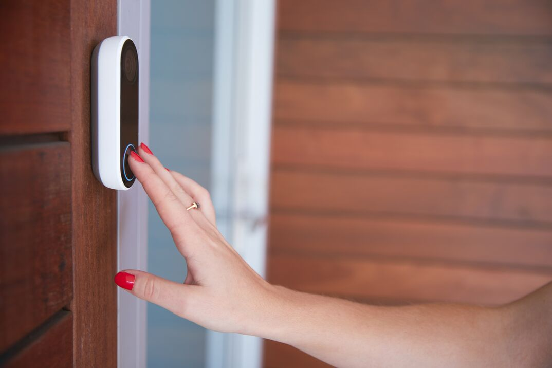 Close Up Of Woman Ringing Front Doorbell Equipped With Security Video Camera