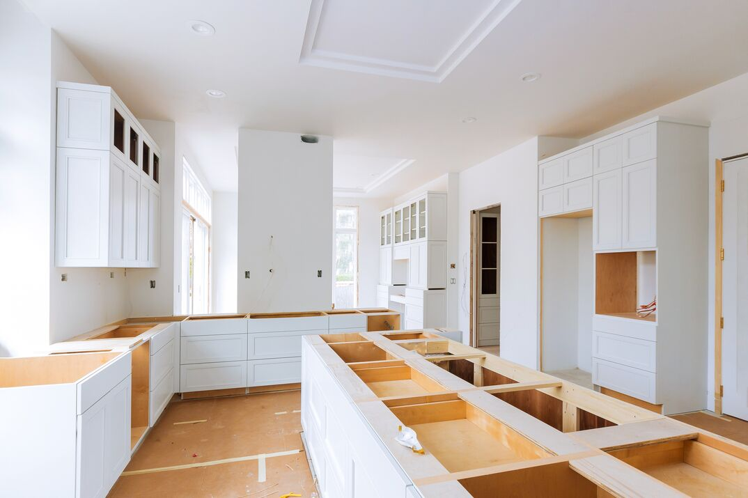 a kitchen remodel in progress using all white cabinetry