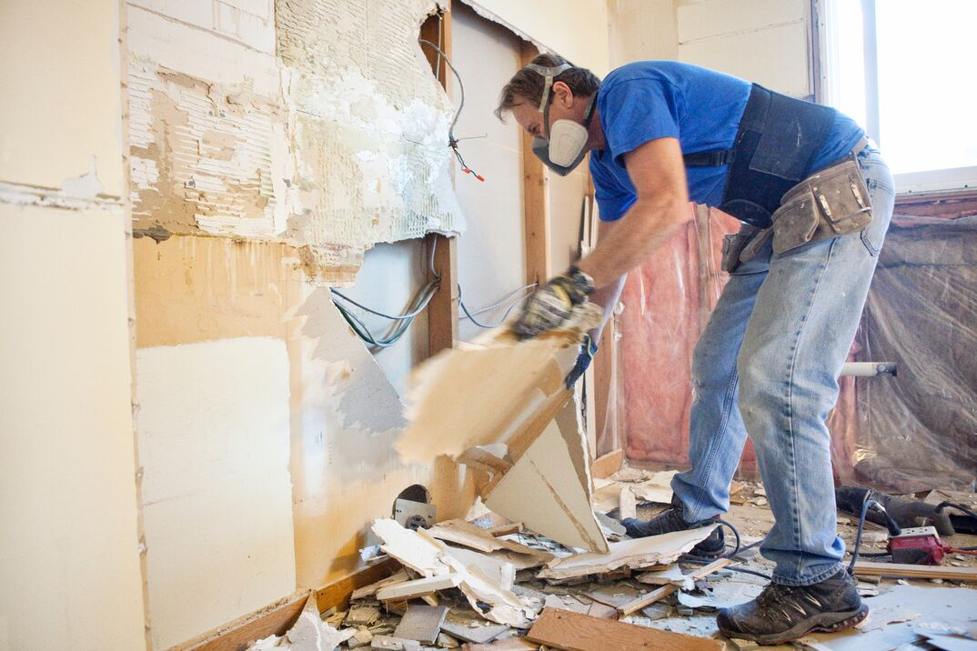 a contractor using PPE carefully demolished a wall in a residential home