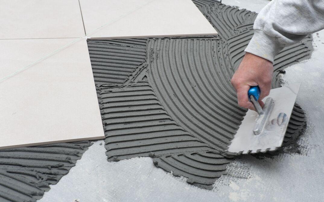 Person scrapes concrete at a construction site