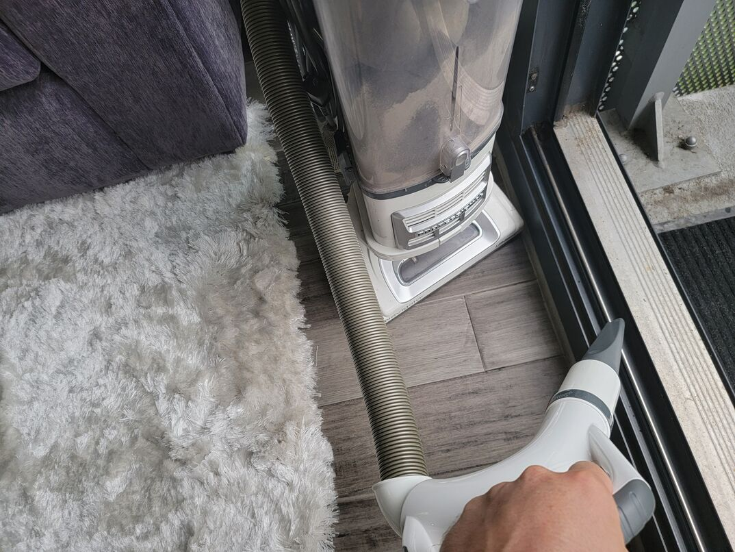 Human hand vacuuming gray metal track of sliding glass door leading from inside room with gray hardwood floors, a white area rug and a gray couch out to a concrete and metal balcony overlooking a green park.