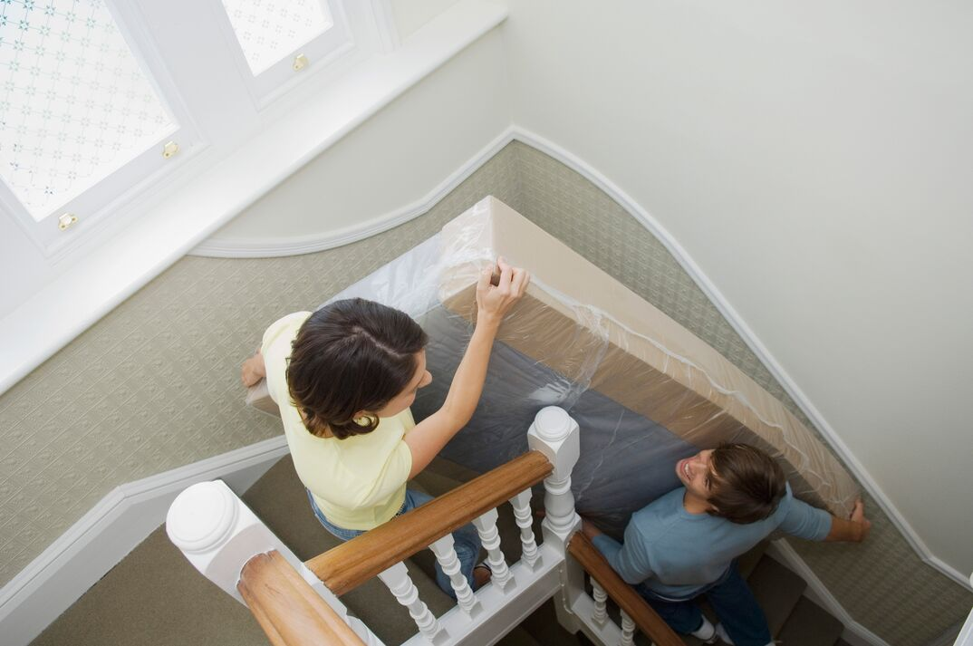 Couple carrying mattress upstairs