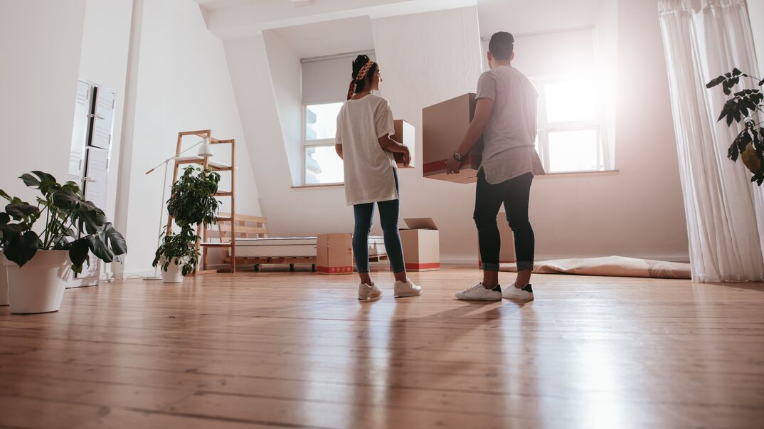 couple dropping off box into their new home