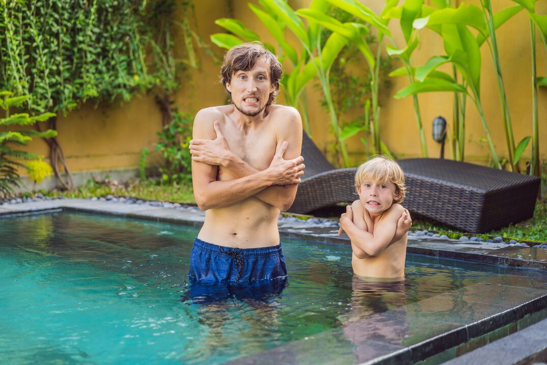 A man and his son shiver in a cold swimming pool