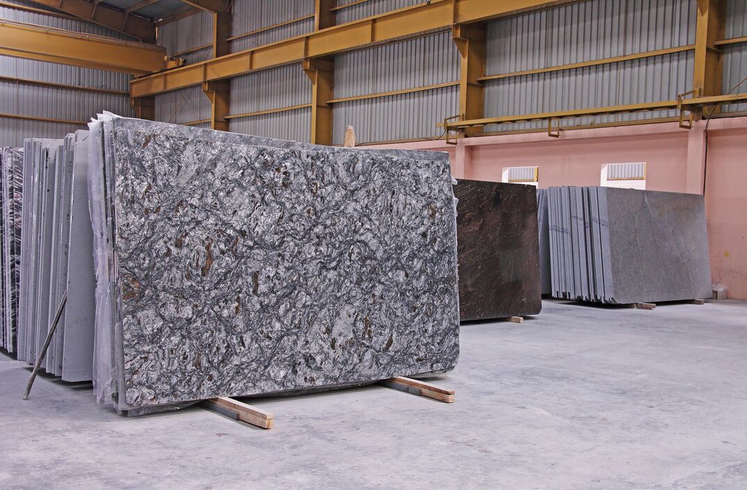 Stacks of different color granite slabs at a warehouse