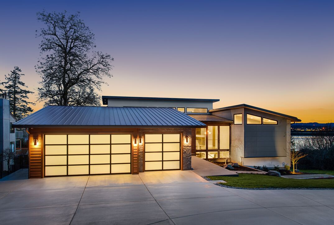 Beautiful modern luxury home exterior at sunset. Features contemporary design and three car garage