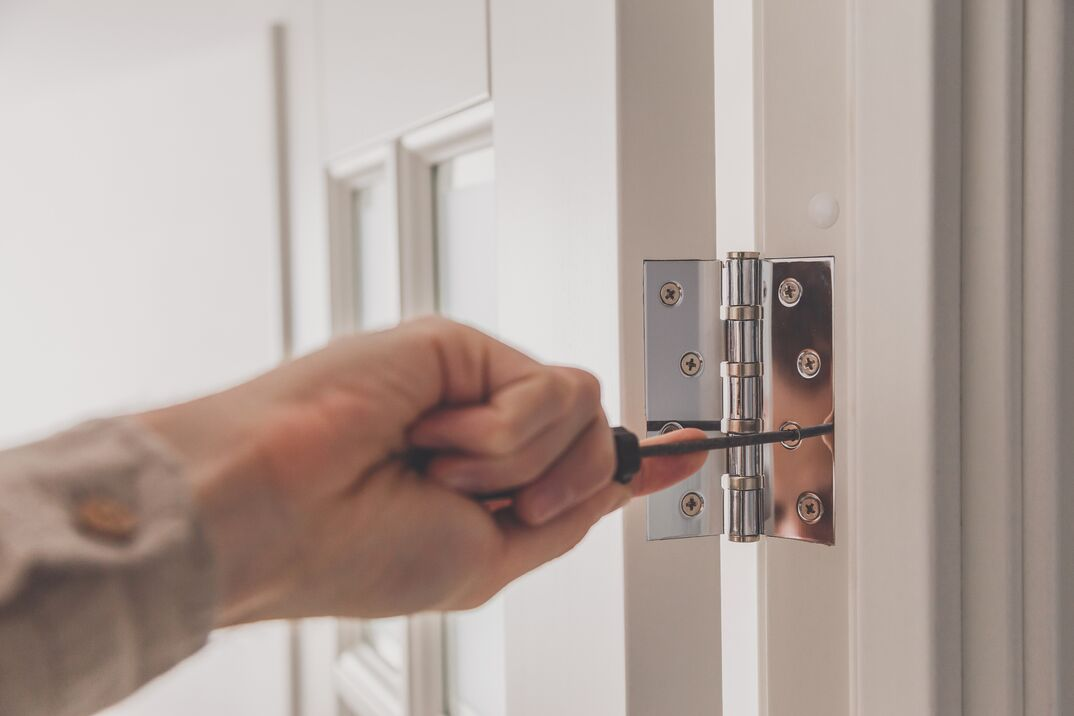 Man remove the door  Twists self-tapping screw with a screwdriver  Stainless door hinges on a white door