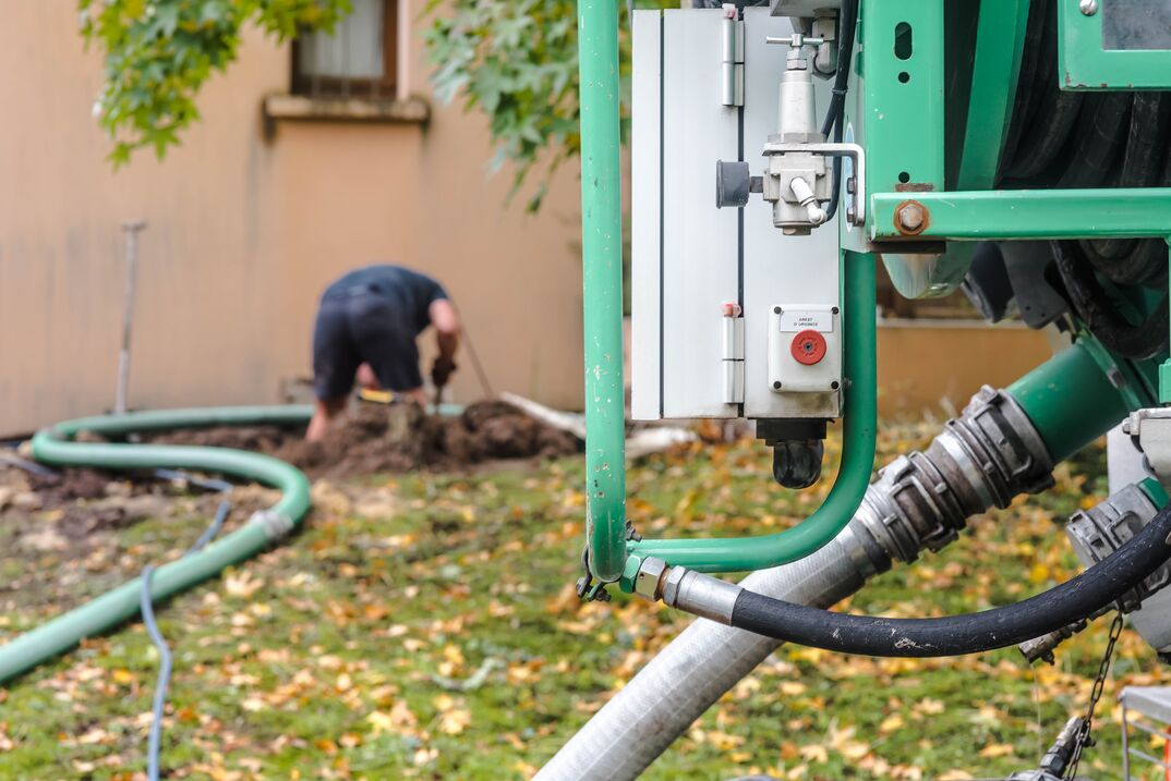 a man is pumping a septic tank from the backyard using a green hose from a large truck