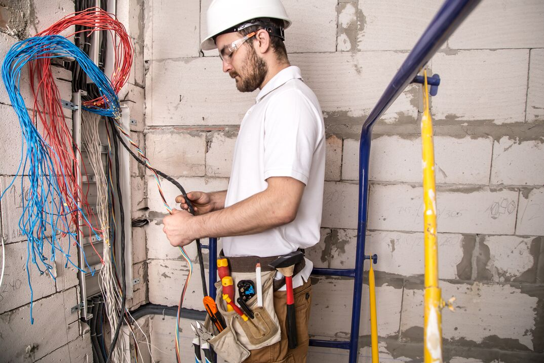 a male electrician in a white shirt and a white heard hat is working on splicing electrical wiring