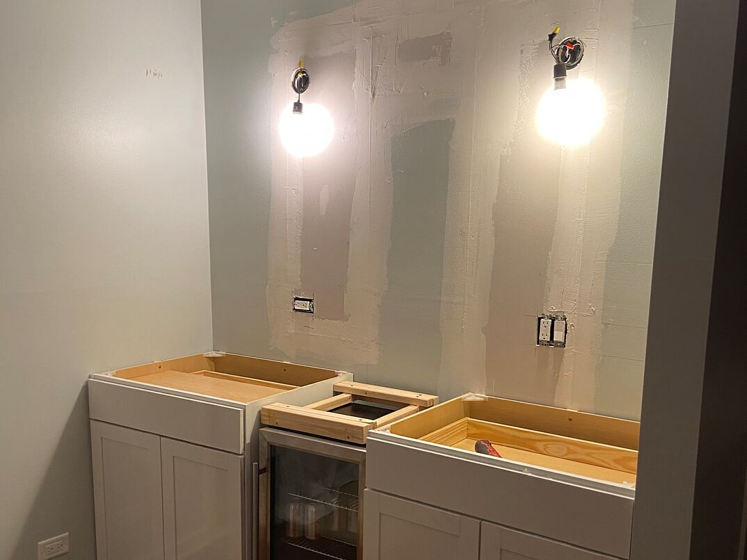 DIY installation of a  dry bar  showing the installation of the shaker cabinets  The temporary lights hang over the unfinished wall