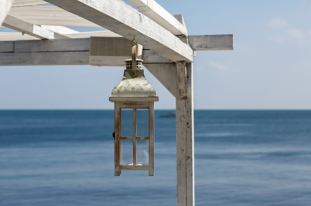 Painted Wooden lantern hangs from a bleached wood pergola overlooking the ocean