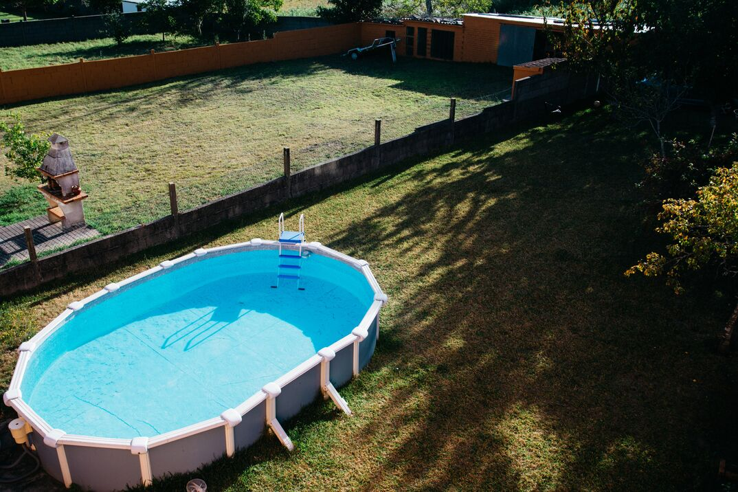 An above ground pool with bright blue water sits in a large and empty backyard.