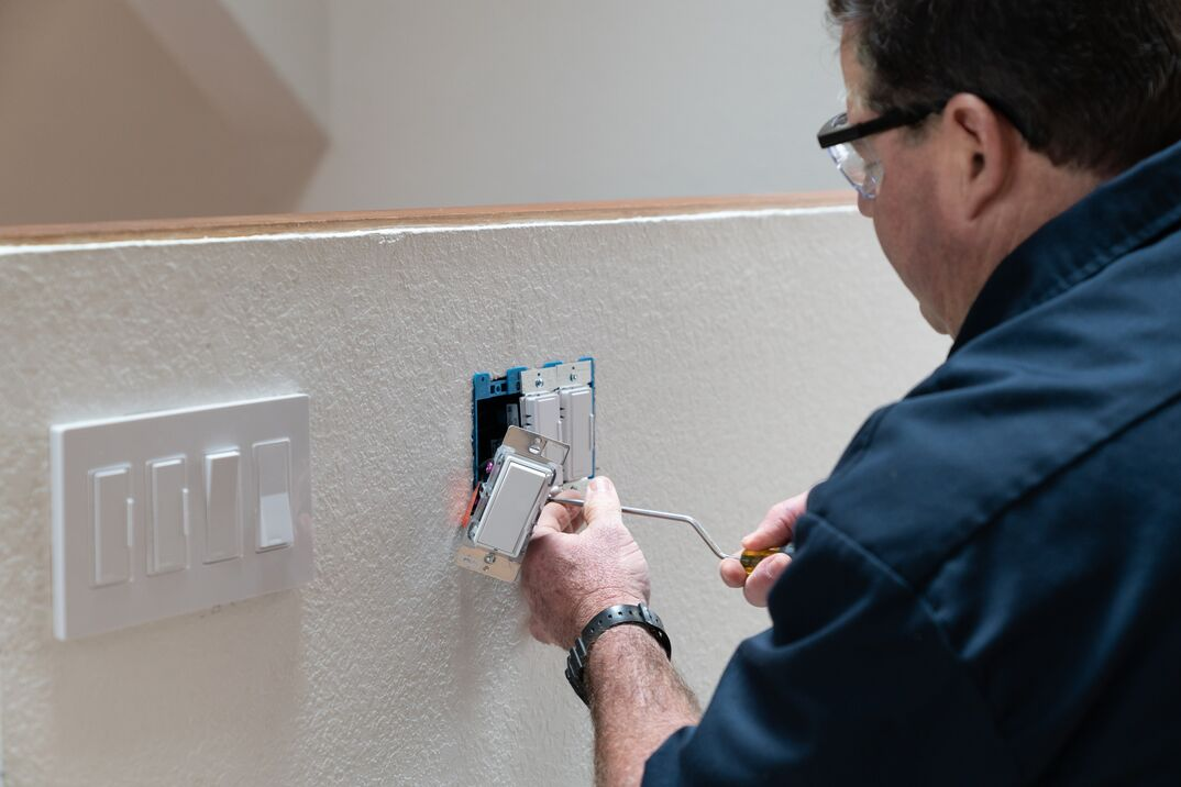 Electrician working in home installing dimmer switched in wall