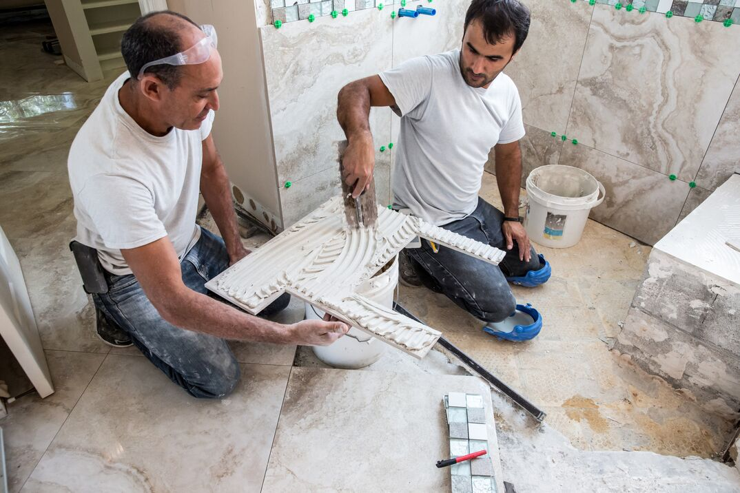 New tile is being installed in shower of a residential home that is being renovated  Two male tile installers are putting cement adhesive on the back of a natural stone tile that will be placed on the wall of the shower