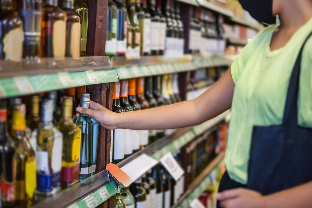 Young female drinker buying alcohol in liquor store