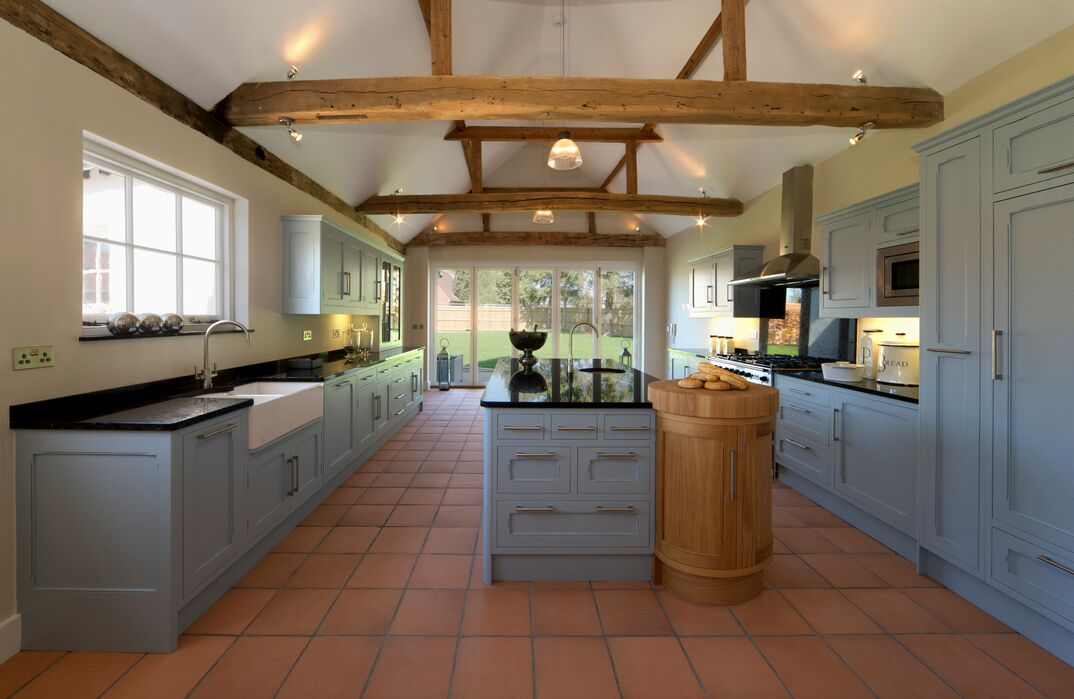 photo of a modern Farmhouse Kitchen with blue cabinets and red terracotta flooring
