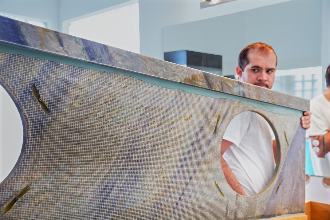contractors install a heavy granite stone countertop