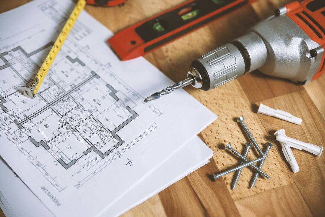 blueprint of a new home with power drill