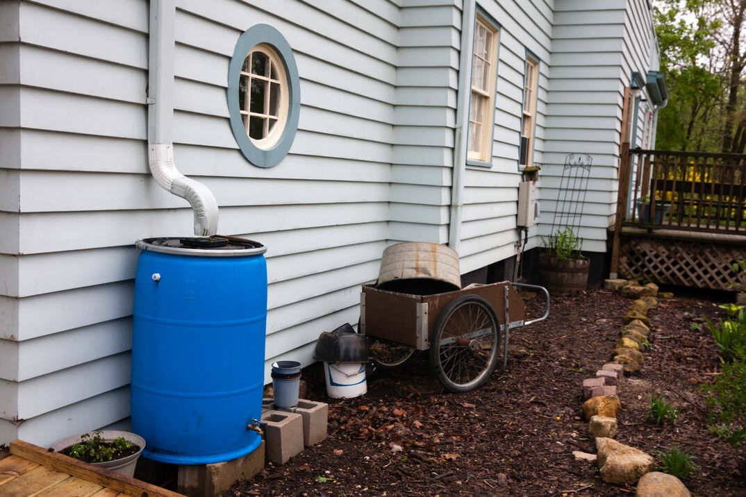 a blue Rain Barrel rests under a white gutter on a home to collect rainwater