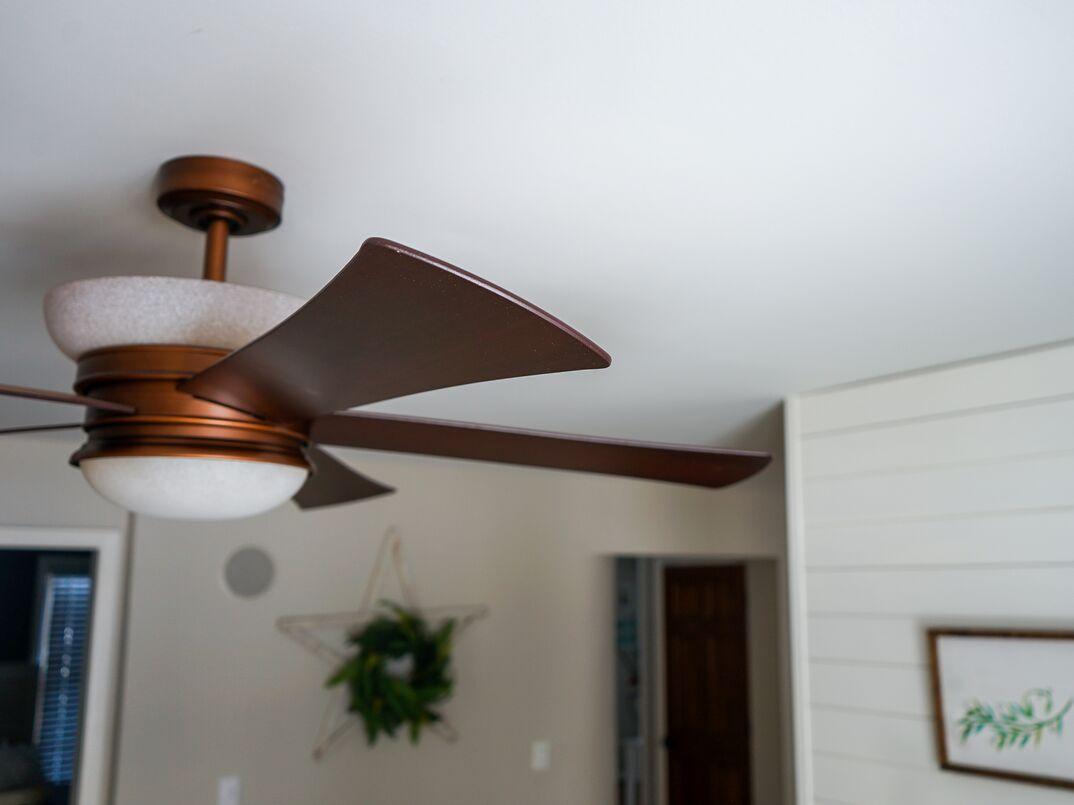 Brown ceiling fan hangs near a neighboring wall