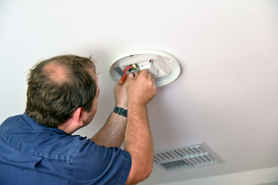 Electrician installing new  ceiling light fixture