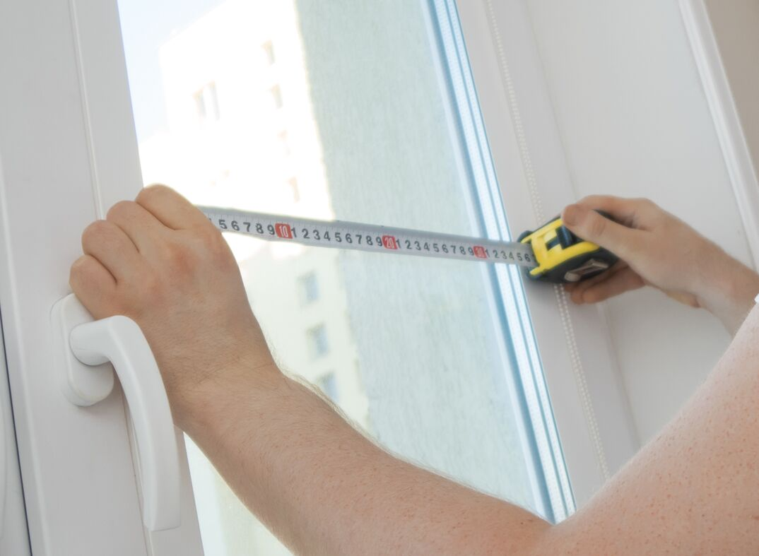 femal hands hold up a tape measure alongside a recently relaced window