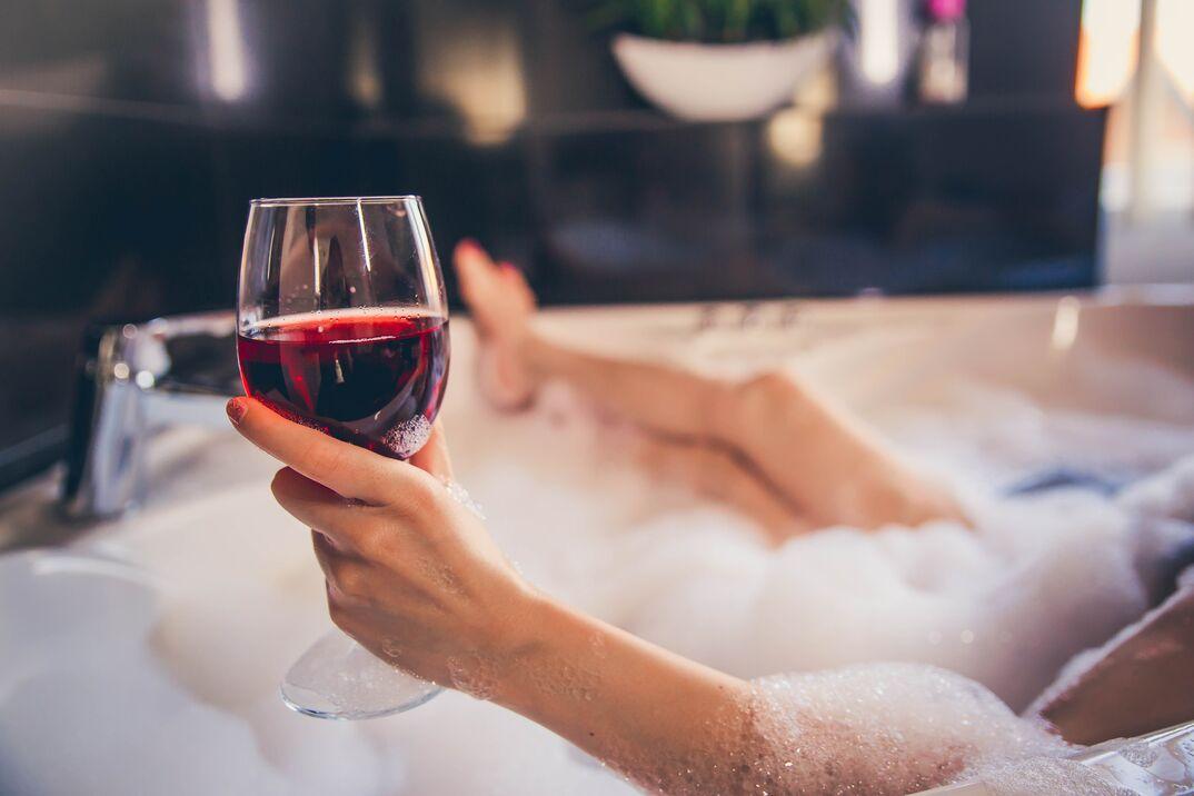 Woman Hand Holding Wineglass In Bathtub