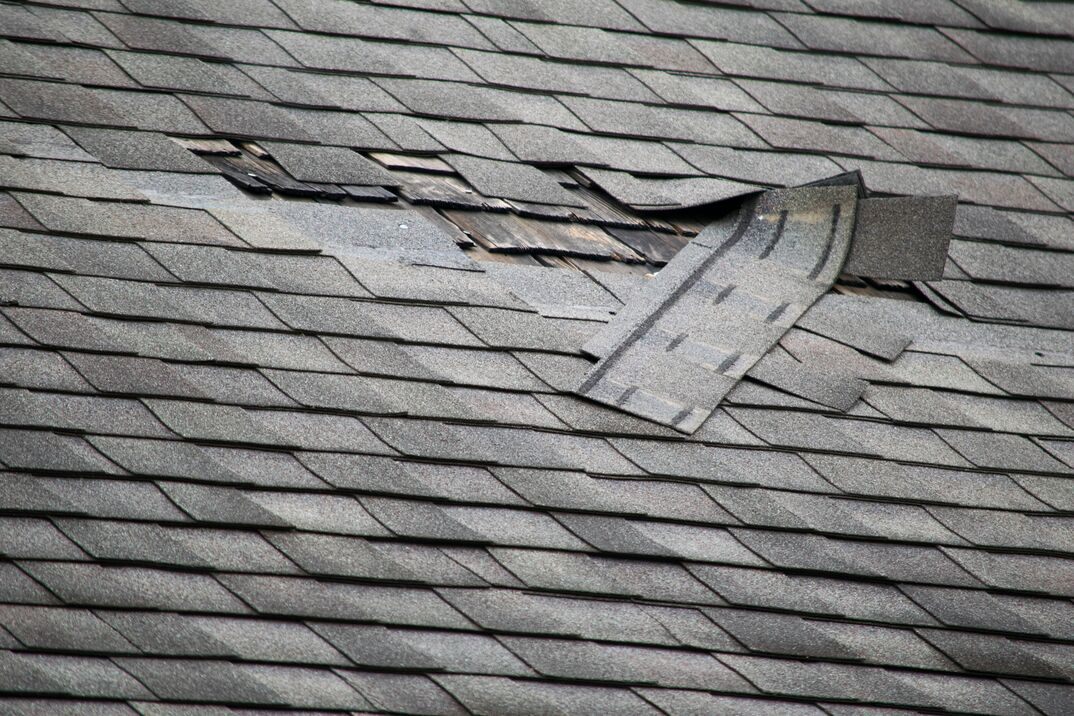 Residential roof with damage to several shingles