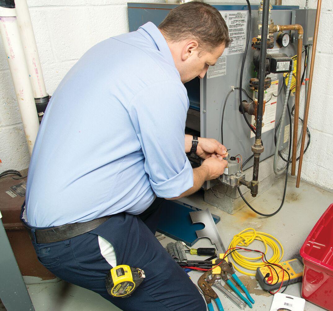 technician fixing furnace