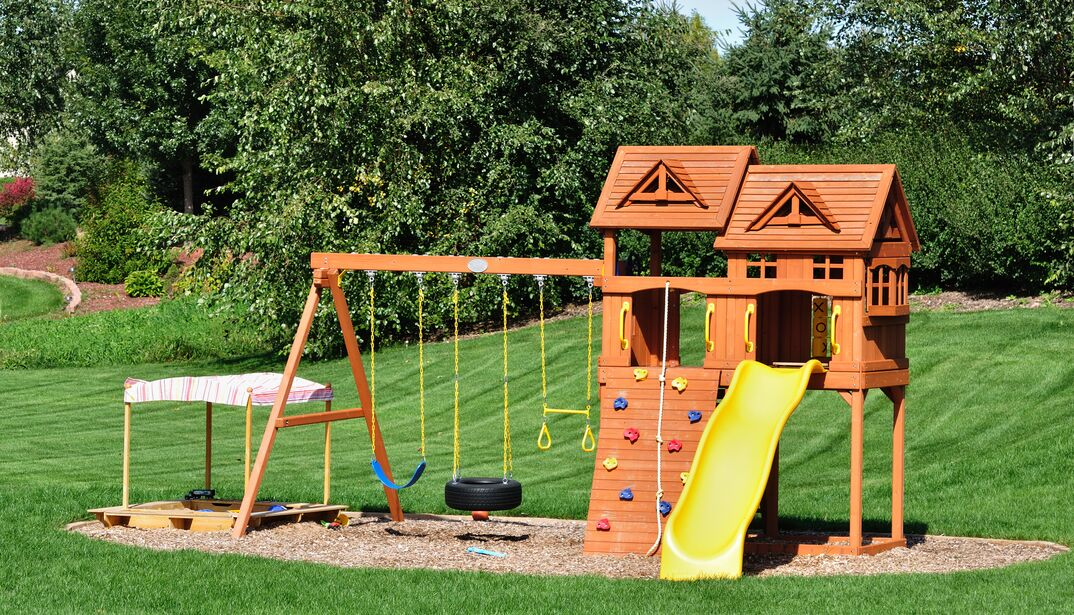 A back yard wooden swing set placed in a garden