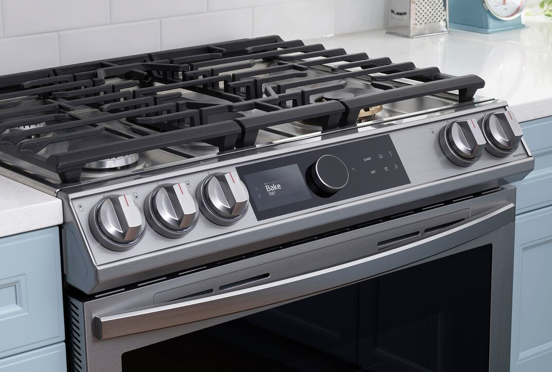 Samsung smart range with black grates on stovetop, a stainless steel frame, black oven door, multiple knobs and a black smart control panel
