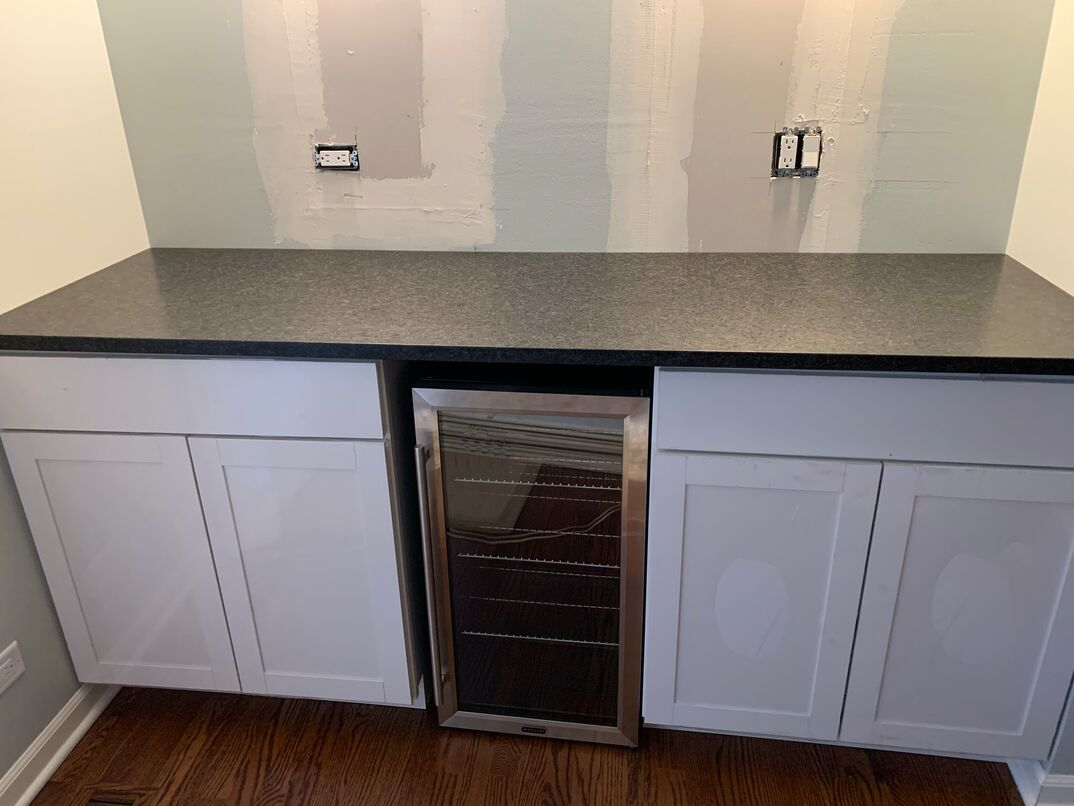 A residential dry bar with a unique  leather  textured black granite counter top