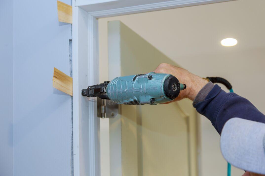 Worker in using air nail gun installing the interior door