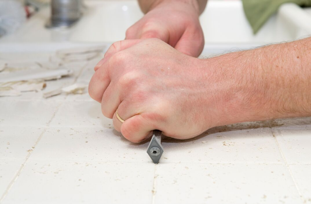 Male hand using a grout removal tool to removing grout from kitchen tiles