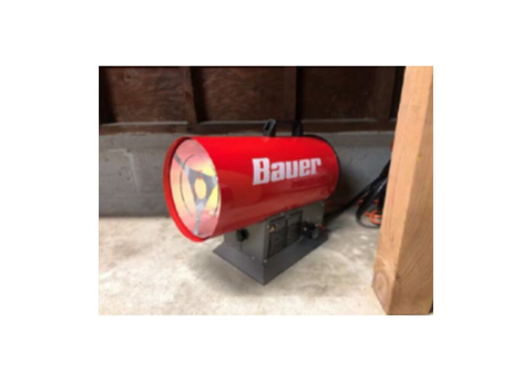 Cylindrical propane heater placed on cement floor